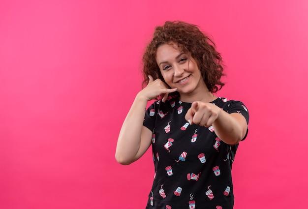 短い巻き毛の若い女性が私をジェスチャーと呼び、前を指で指しています