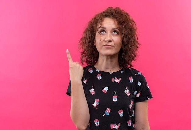 Young woman with short curly hair pointing index finger up thinking looking very anxious standing over pink wall