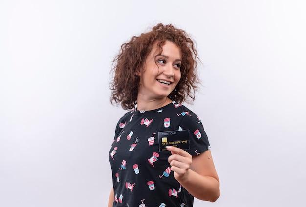 Молодая женщина с короткими вьющимися волосами показывает кредитную карту, глядя в сторону, улыбаясь, стоя над белой стеной