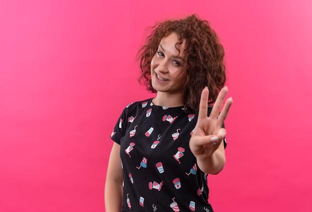 짧은 곱슬 머리를 보여주는 웃고 분홍색 벽 위에 서있는 손가락 3 번으로 가리키는 젊은 여자