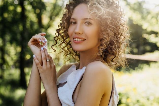 笑顔の短い巻き毛の若い女性