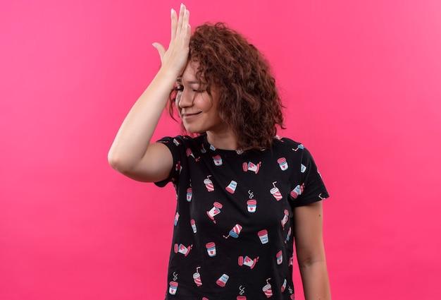 ピンクの壁の上に立っている間違った、忘れて、悪い記憶の概念のために頭に手を置いて立っている短い巻き毛の若い女性