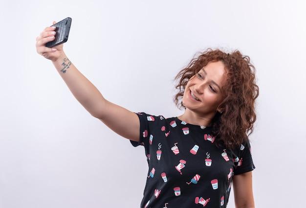 白い壁の上に立っているカメラに微笑んで彼女のスマートフォンを使用してselfieを取る短い巻き毛の若い女性
