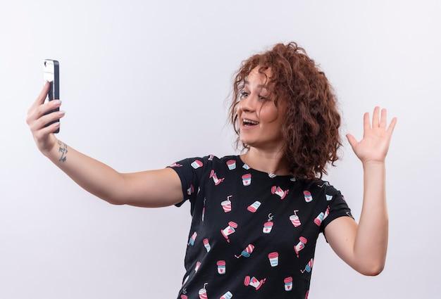白い壁の上に立っている手で手を振ってカメラに微笑んで彼女のスマートフォンを使用して自分撮りを取っている短い巻き毛の若い女性