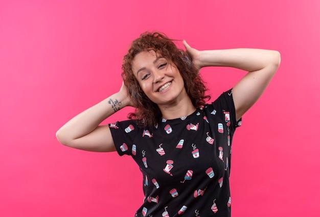 ピンクの壁の上に立って幸せな笑顔で彼女のお気に入りの音楽を楽しんで頭にヘッドフォンで短い巻き毛の若い女性