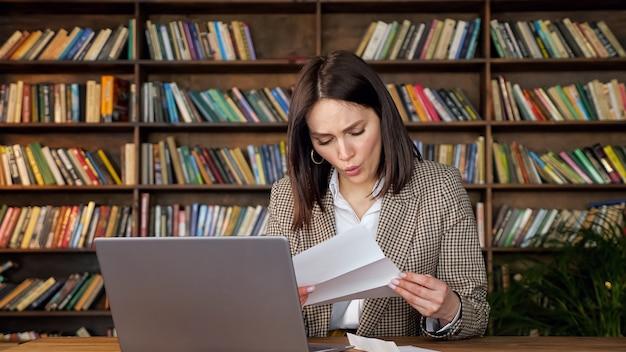 짧은 검은 머리를 가진 젊은 여성이 은행 편지를 열고 집에서 나무 책장에 기대어 노트북에 앉아 충격을 받고 뺨을 만집니다