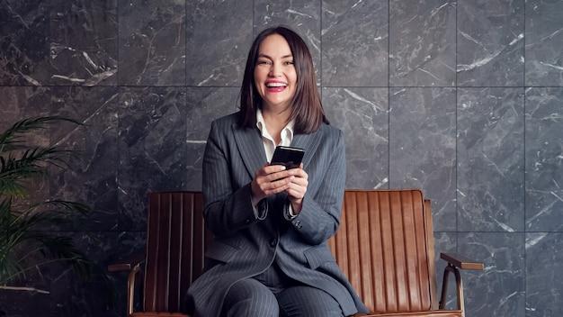 Молодая женщина с короткими типами темных волос на черном смартфоне и счастьем смотрит в камеру, сидя на сером фоне