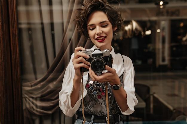 短い髪と赤い口紅の若い女性が写真を作っています。カフェでカメラを保持しているスタイリッシュな白いシャツのポジティブな女性。