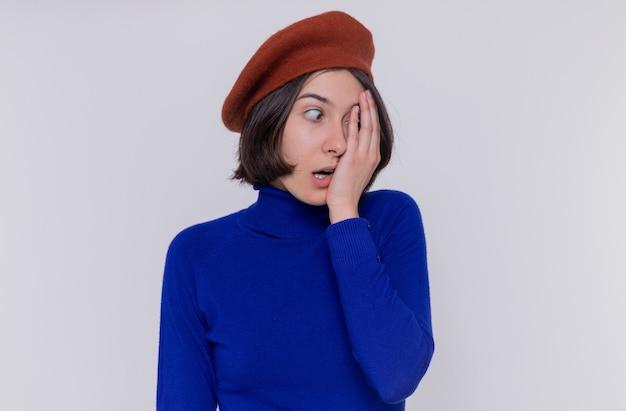 Giovane donna con i capelli corti in dolcevita blu che indossa berretto guardando da parte scioccato che copre un occhio con la mano in piedi sul muro bianco