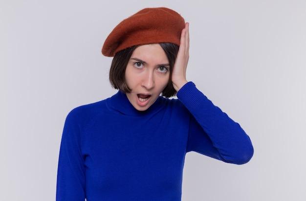 Giovane donna con i capelli corti in dolcevita blu che indossa berretto guardando davanti stupito e sorpreso in piedi sopra il muro bianco