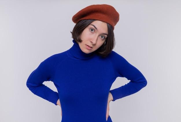 Giovane donna con i capelli corti in dolcevita blu che indossa berretto guardando la parte anteriore con un sorriso scettico sul viso in piedi sopra il muro bianco