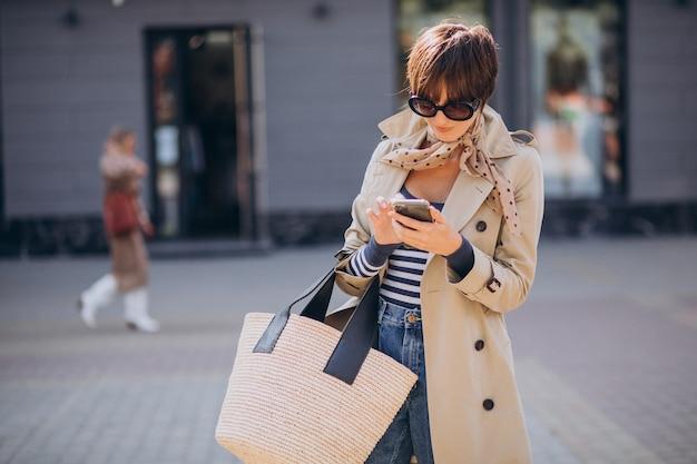 Молодая женщина с короткой стрижкой гуляет по улице