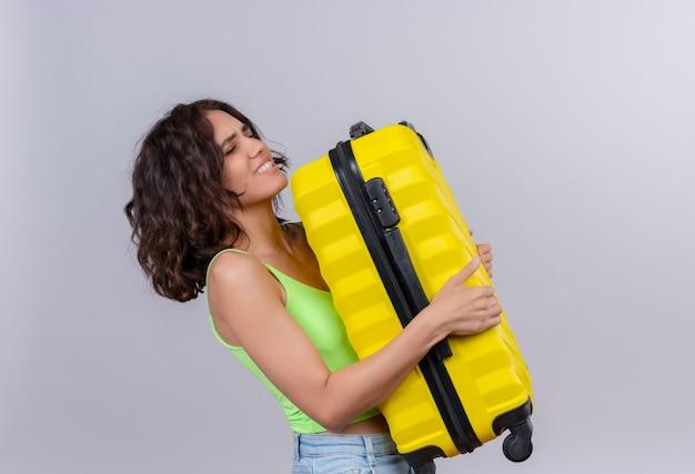 Una giovane donna con i capelli corti in verde crop top che trasporta una pesante valigia gialla su sfondo bianco
