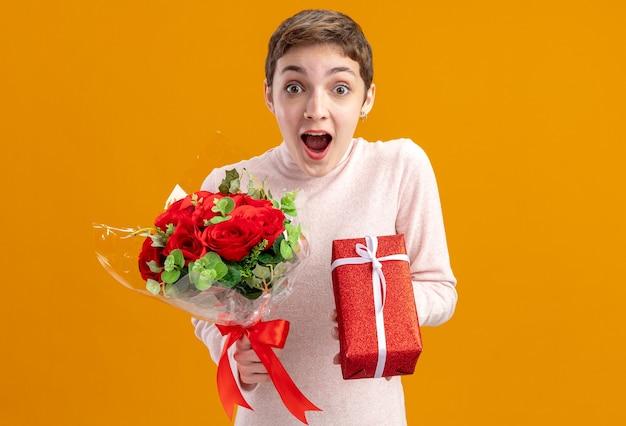 빨간 장미의 꽃다발을 들고 짧은 머리를 가진 젊은 여자와 오렌지 벽에 서 카메라를 놀라게하고 놀란 발렌타인 데이 개념을 찾고 선물