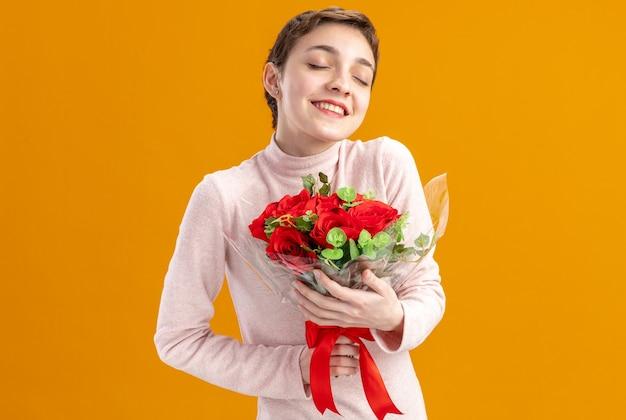Молодая женщина с короткими волосами, держащая букет красных роз, счастливая и позитивная с закрытыми глазами улыбается концепция дня святого валентина, стоящая над оранжевой стеной
