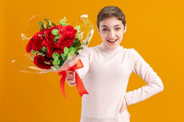 오렌지 벽 위에 서 카메라 행복하고 positivesmiling 광범위하게 발렌타인 데이 개념을보고 빨간 장미 꽃다발을 들고 짧은 머리를 가진 젊은 여자