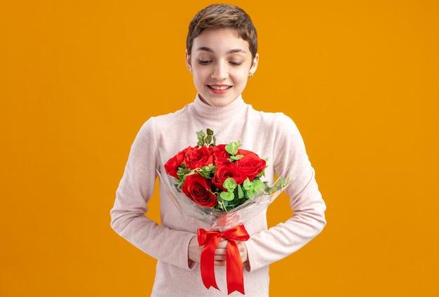 Giovane donna con i capelli corti azienda bouquet di rose rosse guardando le rose con il sorriso sulla faccia felice il giorno di san valentino concetto in piedi sul muro arancione