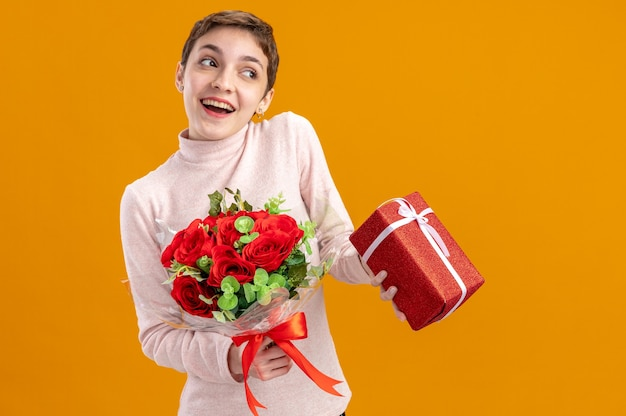 Young woman with short hair holding bouquet of red roses and a present happy and cheerful looking asidesmiling valentines day concept standing over orange wall