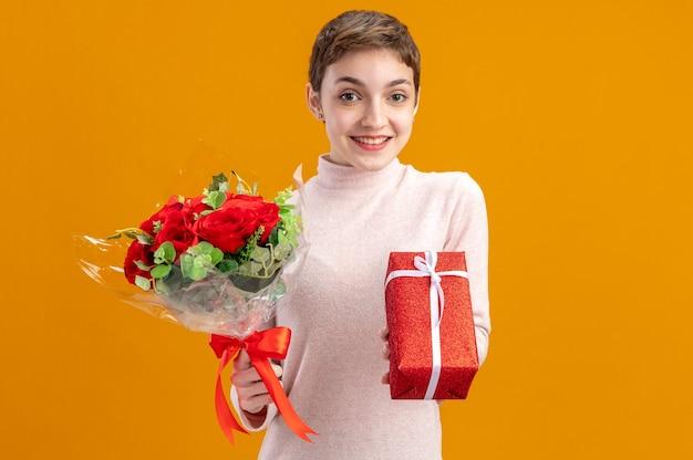 Giovane donna con i capelli corti che tiene il mazzo di rose rosse e un regalo che guarda l'obbiettivo felice e positivo sorridendo allegramente il giorno di san valentino concetto in piedi sopra il muro arancione