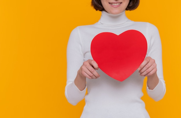 Giovane donna con i capelli corti che tiene il cuore fatto di cartone che sorride allegramente in piedi sopra la parete arancione