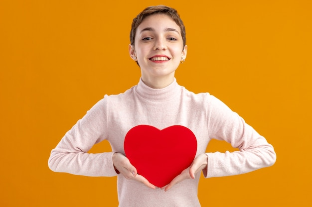 オレンジ色の壁の上に立っている陽気なバレンタインデーのコンセプトを笑顔のカメラを見て段ボールで作られた心を保持している短い髪の若い女性