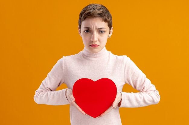 オレンジ色の壁の上に立っている悲しい表情のバレンタインデーのコンセプトを持つ段ボールで作られた心を保持している短い髪の若い女性