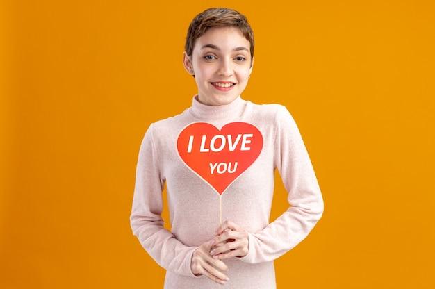 オレンジ色の壁の上に立って元気に幸せでポジティブなバレンタインデーのコンセプトに笑みを浮かべてスティックにハートを保持している短い髪の若い女性