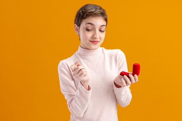 Giovane donna con i capelli corti che tiene scatola rossa e anello di fidanzamento guardandolo con il sorriso sul concetto di giorno di san valentino faccia in piedi sopra il muro arancione