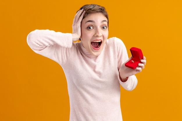 오렌지 벽 위에 서 카메라 행복하고 흥분된 발렌타인 데이 개념을보고 약혼 반지와 함께 빨간색 상자를 들고 짧은 머리를 가진 젊은 여자