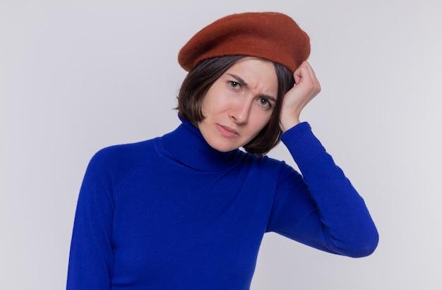 青いタートルネックの短い髪の若い女性は、白い壁の上に立っている彼女の頭に手をつないで混乱し、非常に心配している正面を見てベレー帽をかぶっています