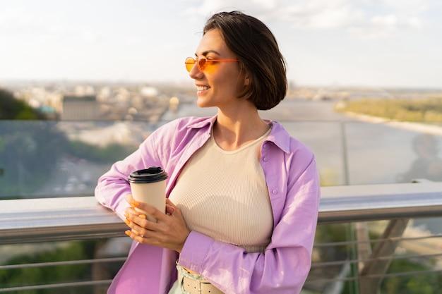 スタイリッシュな夏の衣装で短い髪の若い女性は、現代の橋でコーヒーを飲みます