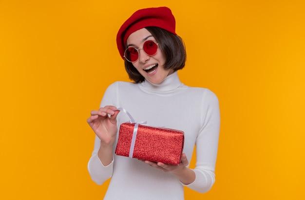 ベレー帽と赤いサングラスを身に着けている白いタートルネックの短い髪の若い女性がプレゼントを持って幸せで興奮してプレゼントを元気に笑顔で開きます