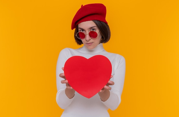 Молодая женщина с короткими волосами в белой водолазке в берете и красных солнцезащитных очках держит сердце из картона, глядя на переднюю улыбку, стоящую над оранжевой стеной