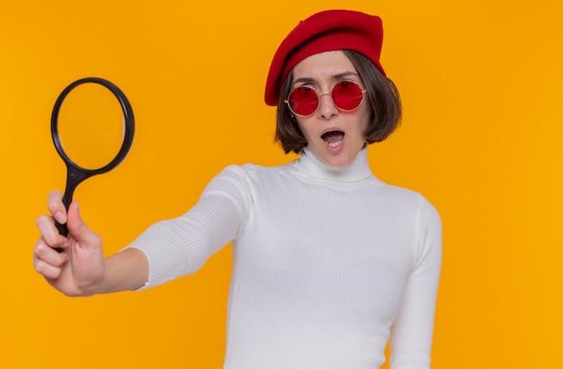 베레모와 돋보기를 들고 빨간 선글라스를 착용하는 흰색 터틀넥에 짧은 머리를 가진 젊은 여자는 오렌지 벽에 놀라고 불쾌한 서