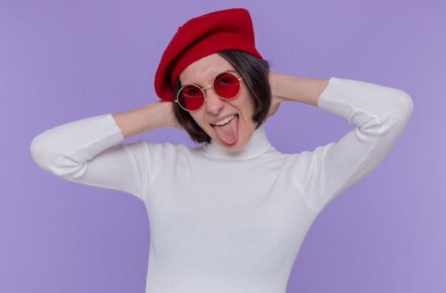 파란색 벽 위에 서있는 혀를 튀어 나와 행복하고 즐거운 전면을보고 베레모와 빨간 선글라스를 착용하는 흰색 터틀넥에 짧은 머리를 가진 젊은 여자
