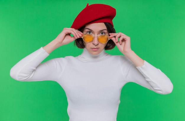 베레모와 노란색 선글라스를 착용하는 흰색 터틀넥에 짧은 머리를 가진 젊은 여자