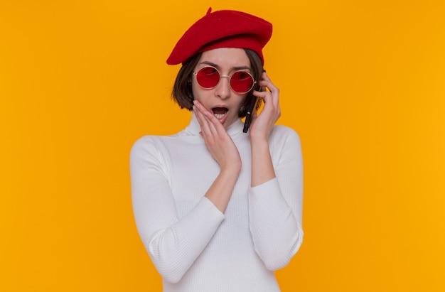 ベレー帽を身に着けている白いタートルネックの短い髪の若い女性
