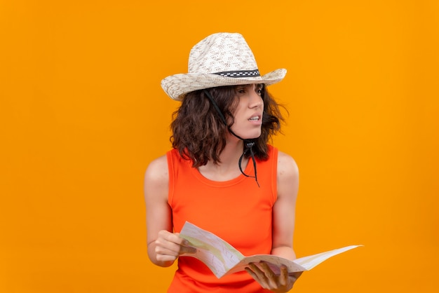 A young woman with short hair in an orange shirt wearing sun hat holding map looking left side