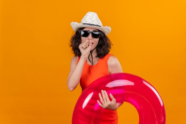 A young woman with short hair in an orange shirt wearing sun hat and sunglasses holding pink inflatable ring