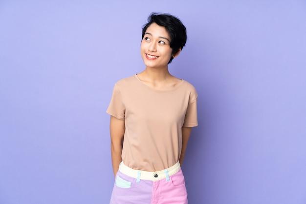 見上げながらアイデアを考えて孤立した紫の上の短い髪の若い女性
