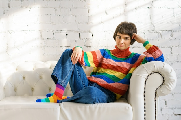 A young woman with short hair in a rainbow sweater and socks is sitting on a white sofa, the concept of sexual minorities