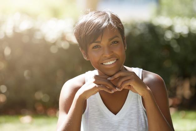 Молодая женщина с короткими волосами, сидя в парке