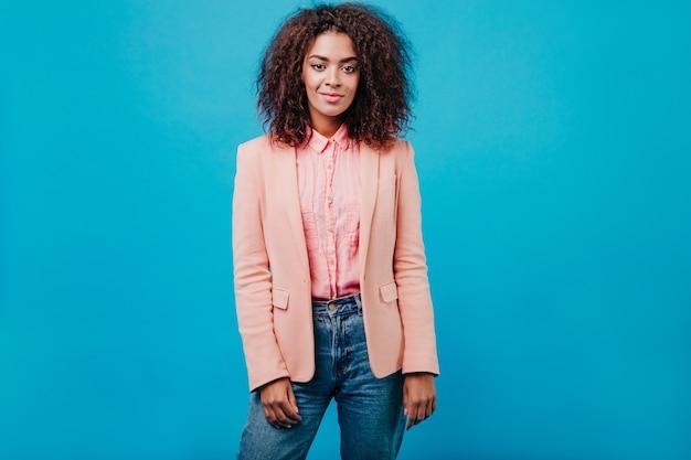 파란 벽에 서있는 짧은 머리를 가진 젊은 여자