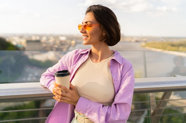 Young woman with short hair in styish summer outfit drink coffe on thr modern bridge