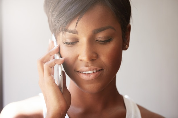 Молодая женщина с короткими волосами разговаривает по телефону