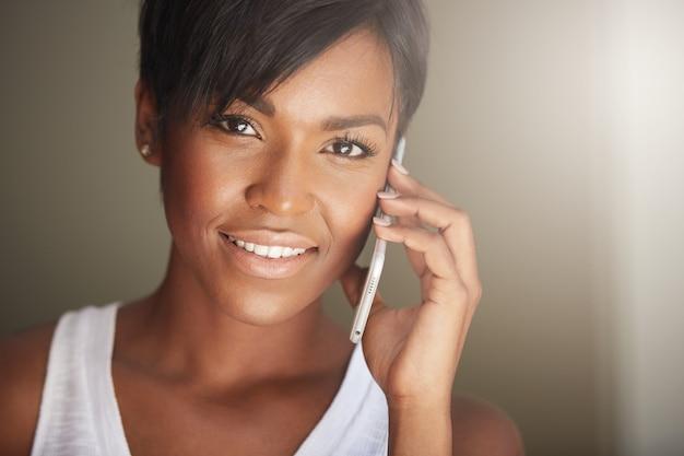 電話で話している短い髪の若い女性