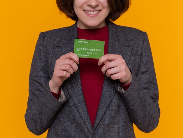 Young woman with short hair wearing grey jacket holding credit card