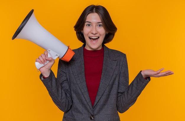 오렌지 벽 위에 서 행복하고 놀란 전면을보고 확성기를 들고 회색 재킷을 입고 짧은 머리를 가진 젊은 여자