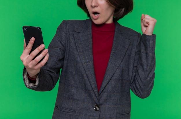 興奮している握りこぶしを握っている灰色のジャケットを着ている短い髪の若い女性