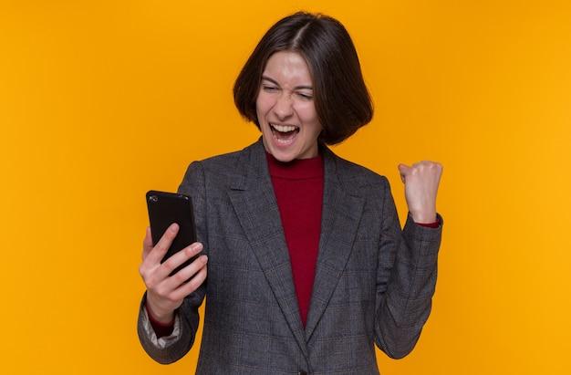 灰色のジャケットを着た短い髪の若い女性は、スマートフォンを握りこぶしを握りしめて幸せで興奮して元気に笑っています